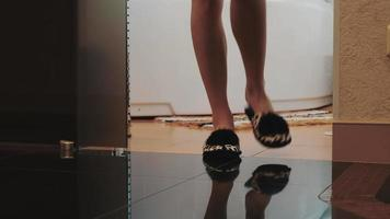 View of young woman in slippers stand up from bath and walk out bathroom video