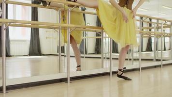 Mädchen posiert auf einem Bein bei Ballettbarre