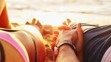 couple main dans la main sur une plage au coucher du soleil
