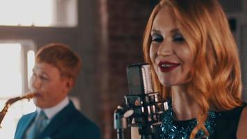 chanteur aux lèvres rouges sur scène au microphone avec le saxophoniste. le jazz