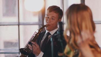 jolie chanteuse de jazz sur scène avec le saxophoniste. Danse. projecteurs