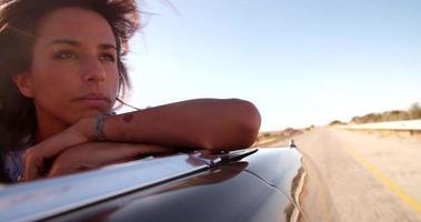 ragazza stile boho all'aperto con auto decappottabile al tramonto