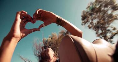 Hipster-Mädchen posiert für Foto, das Handherz macht