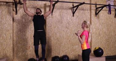 uomo e donna nello sport della palestra che esercita ragazzo che tira alla formazione della palestra della barra orizzontale, atleta del timer della stretta della ragazza che risolve