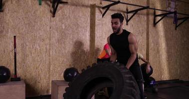 homem praticando ginástica esporte cara jogando pneu grande treino de ginástica, esportista malhando video