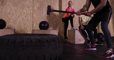 uomo in palestra sport che esercita ragazzo ha colpito allenamento in palestra grande pneumatico, sportivo che lavora fuori