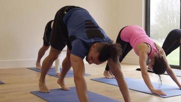lezione di yoga che si estende su stuoie in classe girato su r3d video