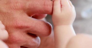 mão de adulto segurando as mãos de bebê video