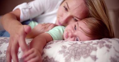neonato con gli occhi azzurri con sua madre sul letto