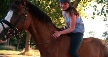 Mädchen auf ihrem Pferd mit goldener Sonne flackern durch Blätter