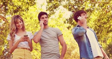 amici felici che usano i loro smartphone nel parco