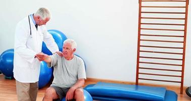 lächelnder Arzt hilft dem Patienten, seinen Arm und seine Schulter zu bewegen