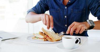 uomo che mangia pranzo con caffè
