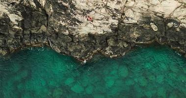 Aerial view cliff jumping into ocean
