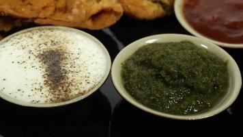 close-up de um prato de samosa servido com chutney da Índia branco, verde e vermelho