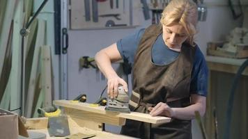 weibliche Holzarbeiterin, die Holzbrett schleift