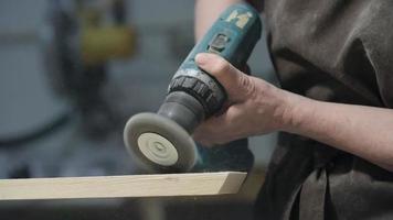 donna con smerigliatrice angolare su legno