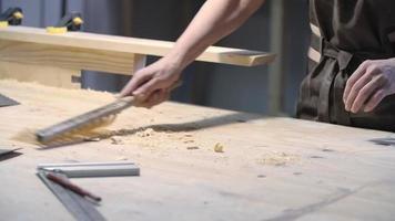 falegname che pulisce i trucioli di legno