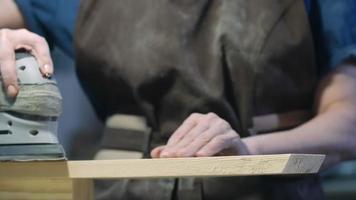 Carpintero femenino con lijadora de madera