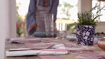 colpo a livello di superficie della donna che prepara la tavola da pranzo sul patio, girato su r3d