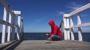 giovane donna utilizzando cellulare smart phone al molo sull'oceano