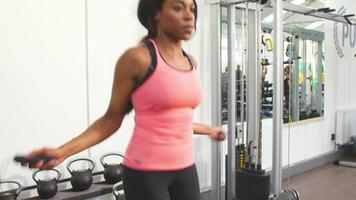 Young African American woman skipping at a gym