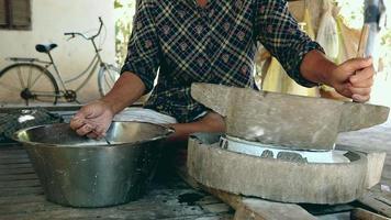Piedra de molino torneada a mano en uso para hacer harina de arroz remojada