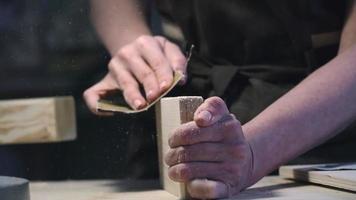 mãos femininas lixando madeira video