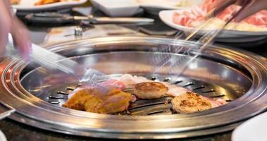 Zeitraffer von Menschen, die Speck, Schweinefleisch und Hühnchen im koreanischen Grillstil im Restaurant essen