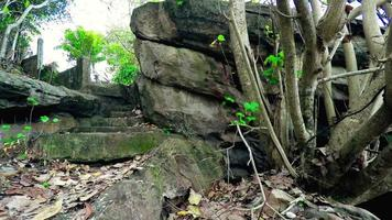 estructura de piedra antigua con escalones que conducen a la ladera de una colina.