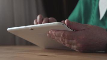 Close up of a white tablet PC in aged woman hands - Side view
