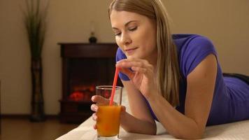 bela jovem deitada em um sofá bebendo suco em um copo