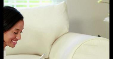 donna felice che invia testo sul divano