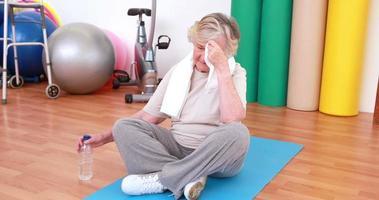 mujer mayor cansada en colchoneta de ejercicios