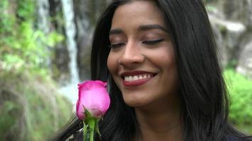 linda mulher hispânica com flor rosa