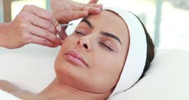 femme à l'aide de pincettes sur le sourcil du patient