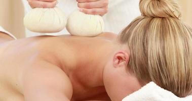 mulher desfrutando de uma compressa de massagem com ervas