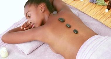Woman enjoying a hot stone massage video
