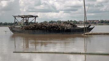 Poteaux de bambou posés dans le sens de la largeur sur une barge stationnaire sur une rivière