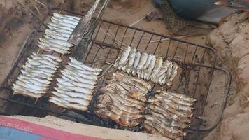 churrasco no chão com peixe grelhado e com pinça de cozinha
