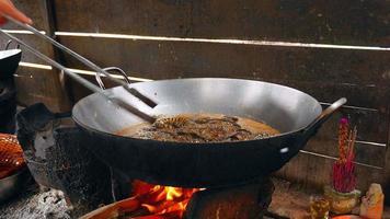 serpents frits au wok cuisson à l'aide de pinces