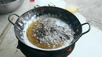grenouilles mortes plongées dans de l'huile bouillante pour la cuisson