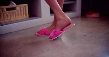 Woman wearing pink slippers in house video