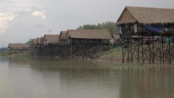 Tidy row of waterfront stilt-houses with rain falling over lake