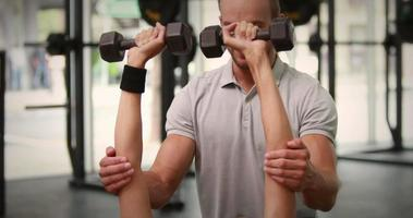 Colocar mujer levantando pesas con entrenador video