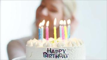 glückliche Frau, die Kerzen auf Geburtstagstorte ausbläst