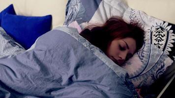 mujer en la cama despertando y abriendo los ojos