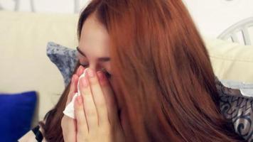 femme malade au lit éternuements dans du papier absorbant