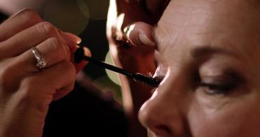 maquilladora aplicando rímel en ojos de mujer. video