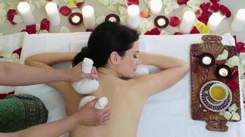 Mujer en spa resort masaje bolsas de hierbas aromáticas